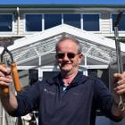 Clutha Vets veterinarian John Smart handles some obsolete tools — hand clippers and spay scissors...