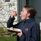 Balmacewen Intermediate pupil Lyla (13) takes a bite of the pancakes her class made to raise...