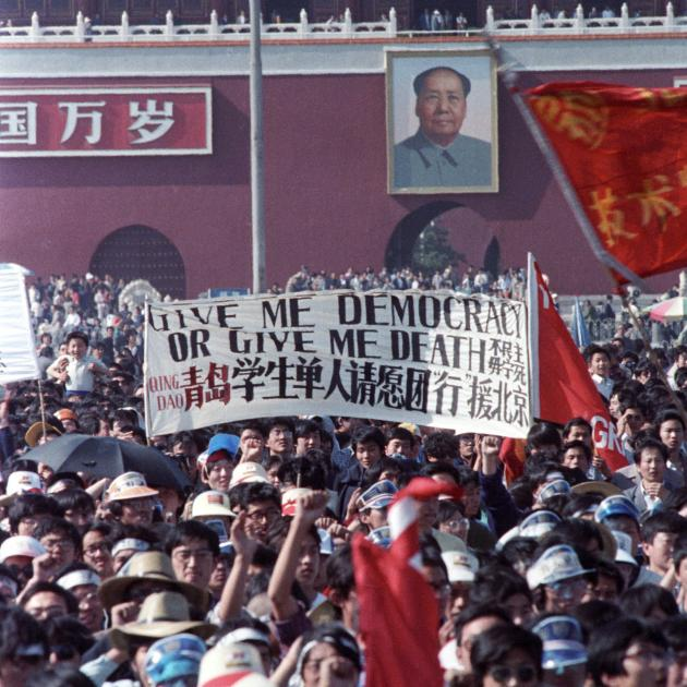 """Students carry a sign that reads, """"Give me democracy or give me death,"""" during a demonstration in..."""