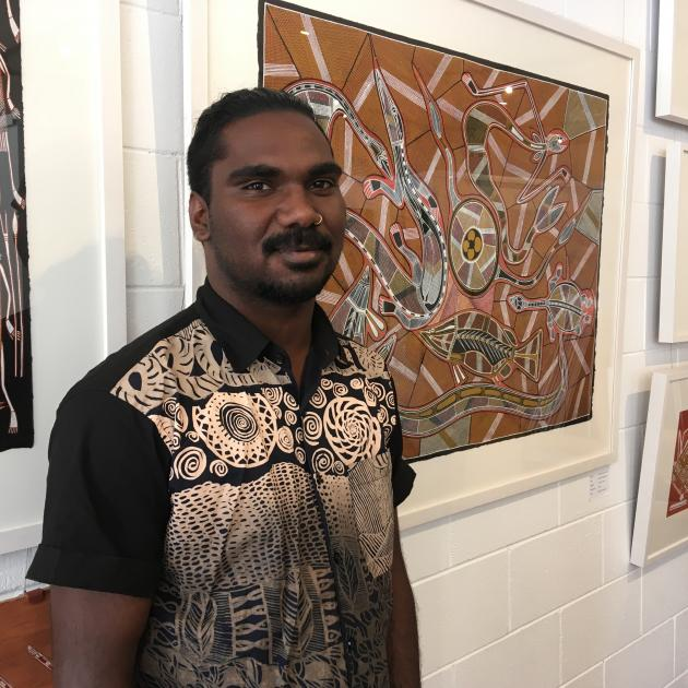 Artist Rodriguez Wilson is flanked by some of his artworks at Provenance Arts, in Darwin. The...