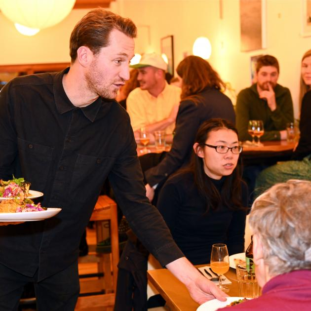 Everybody Eats founder Nick Loosley serves dinner at Kind Company on Friday night. PHOTOS: LINDA...