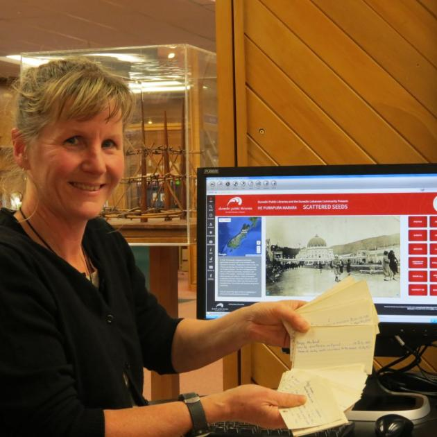 Emma Milburn shows the old index cards, which Dunedin Public Libraries has  begun to digitise, in front of the  recollect home page where the archived material will be able to be  accessed. Photo by Joshua Riddiford