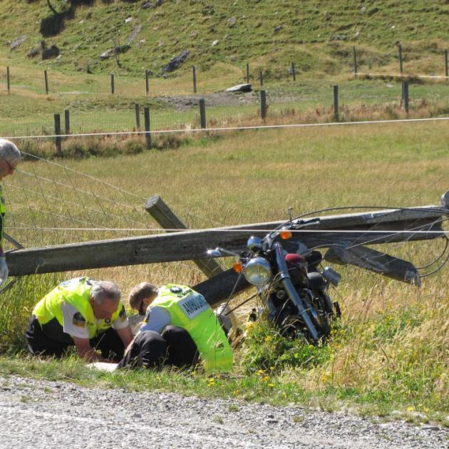 Emergency workers attend to an injured Christchurch motorcyclist (lying in ditch) who crashed his motorbike into a power pole near Makarora yesterday morning and landed on power lines. Photo by Lucy Ibbotson.