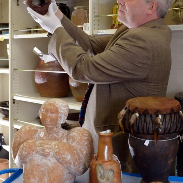 Otago Museum director Dr Ian Griffin examines a salt container, created by potter Barry Brickell and used by Dunedin artist Ralph Hotere and kept on a shelf above his oven. The other ceramics in the foreground are also part of the collection. Photo by Ger