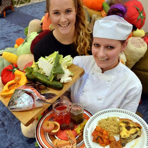 Otago Polytechnic third-year bachelor of culinary arts student Rebecca Lamb (left)  holds the raw ''waste food''  used to make the menu items  held by second-year student  Phillipa Seymour. PHOTO: STEPHEN JAQUIERY