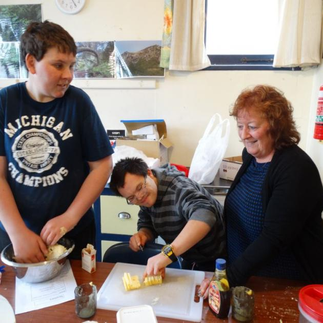 From left: Josh Anderson (19) and Rhys Walsh (21) mix up a batch of date scones with Sara Cohen principal Raewyn Alexander. PHOTO: ELEANOR AINGE ROY