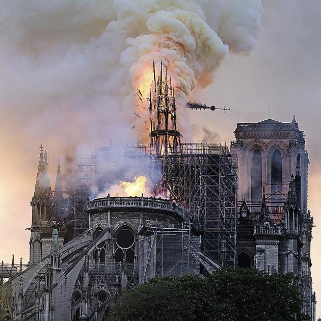 Flames and smoke rise as the 91-metre-high spire on Notre Dame cathedral collapses. Photo: AP