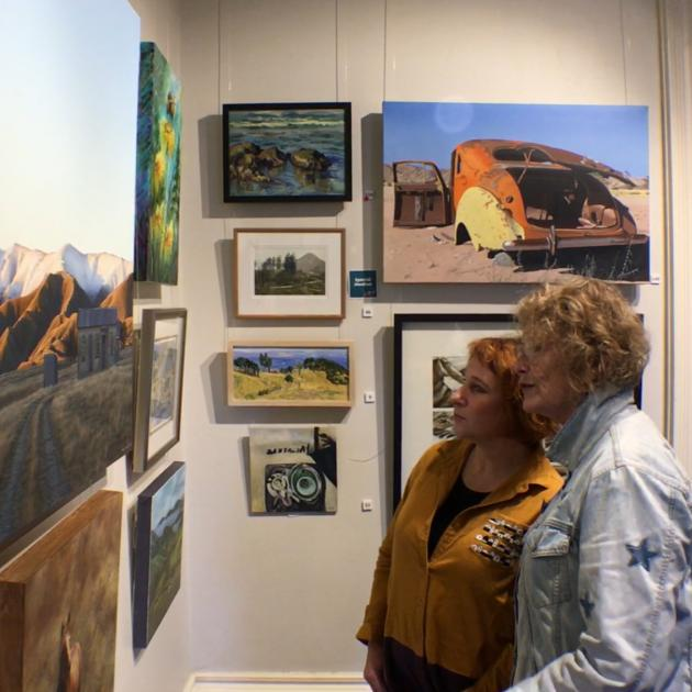 Otago Art Society members Anne Baldock (right) and Ness Kerr admire some of the paintings on display. Photo: Rudy Hueting