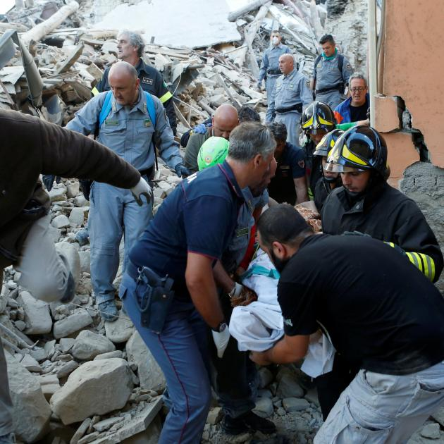Rescuers carry a person on a stretcher following a quake in Amatrice, central Italy. Photo: Reuters