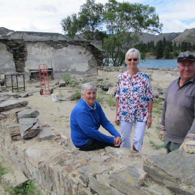 Old Cromwell Inc Society board members Helen Scoles (left) and Estelle Scott stand with heritage stonemason Keith Hinds, of St Bathans, at the restoration work on walls of the old Athenaeum Hall in the Cromwell Heritage Precinct. Photo: Pam Jones