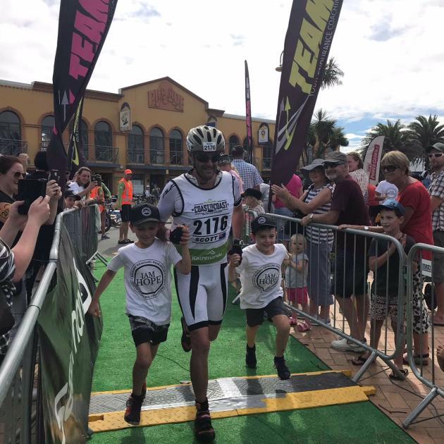 Scott Weatherall,  of Dunedin, runs to the finish line of the  Coast to Coast with sons Thomas ...