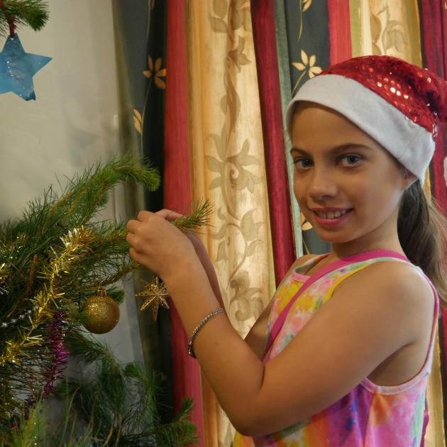 Ariah Gillon-Smith adds a  star decoration to her family's Christmas tree. PHOTO: JESSICA WILSON...