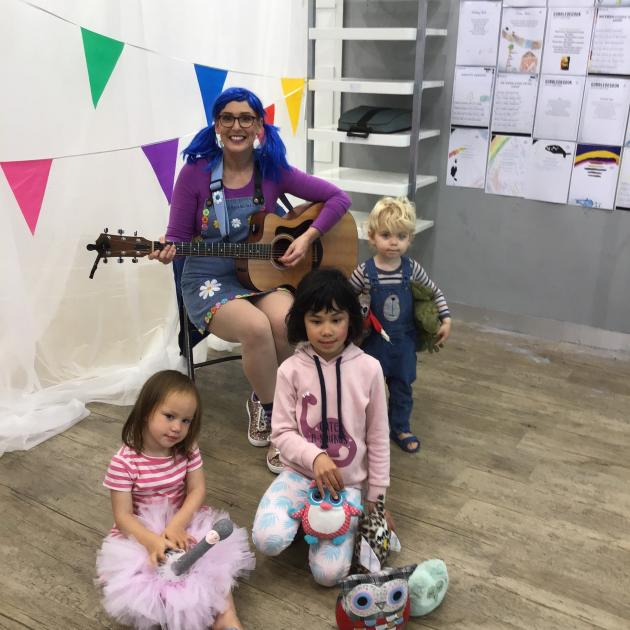 Children's musician ShellyJ plays for little visitors (from left) Wairaka Pouwhare (3), Celine...