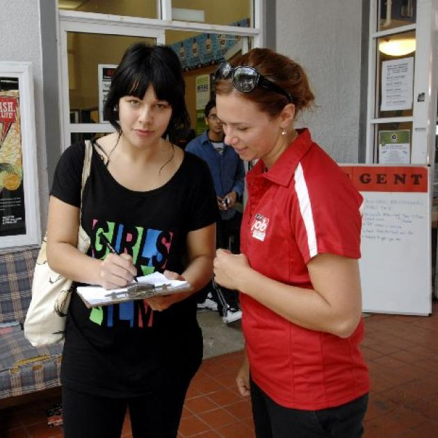 Sasha Ward-Faint (18) (left) fills out an enrolment form assisted by Lucy McAuliffe (21) from Student Job Search. Photo by Linda Robertson.