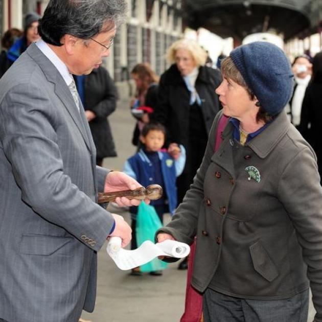 Dunedin Mayor Peter Chin receives the climate change relay baton and register of baton bearers...