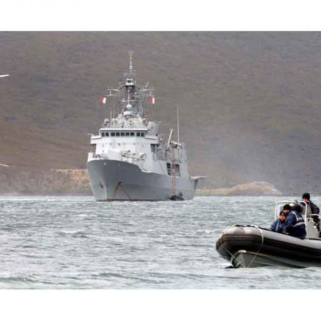 A Seasprite helicopter from New Zealand frigate HMNZS Te Kaha ferries sections of boardwalk on to...