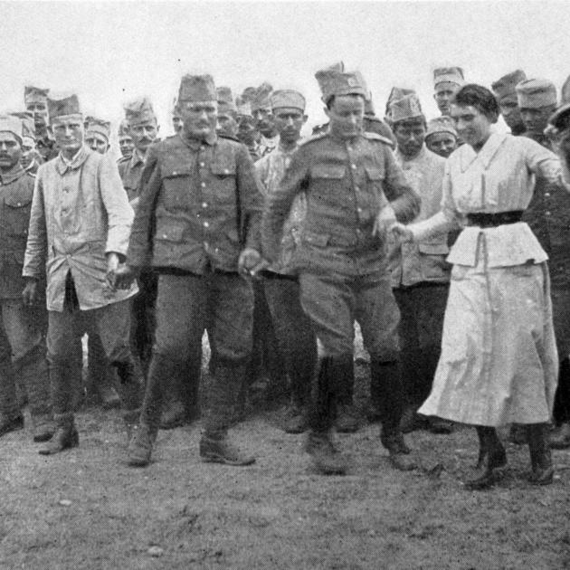 """Serbian troops at Salonika dancing the """"hora'' - a dance that lasts all day. The band is seated..."""