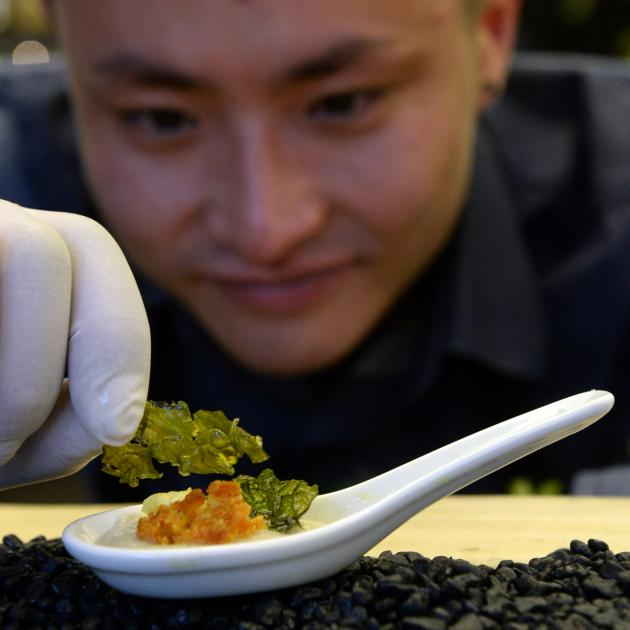 Otago Polytechnic third year bachelor of culinary arts student Dawoo Jeong (25) places toasted kale garnish on a cauliflower entree at the bachelor of culinary arts Excite 2016 showcase last night. Photo by Lidna Robertson.