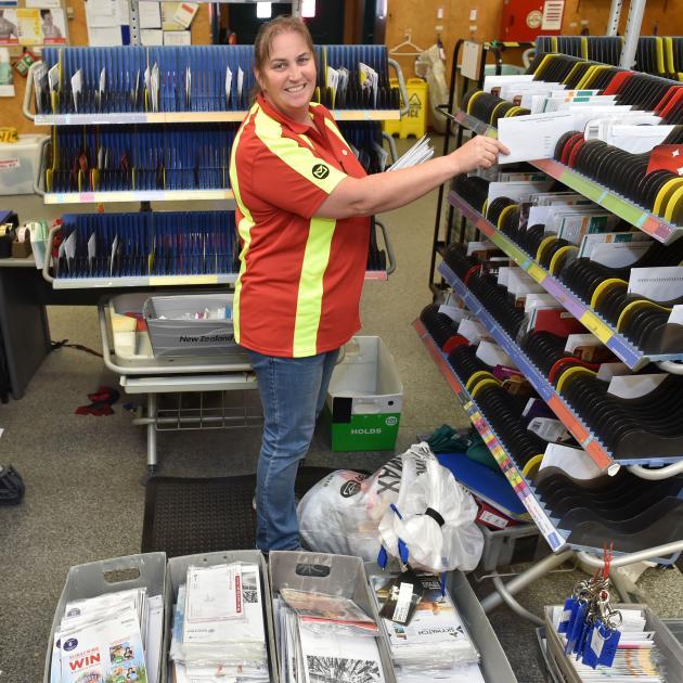 New Zealand Post South Dunedin depot team leader Nicki Templeton sorts through some of the...