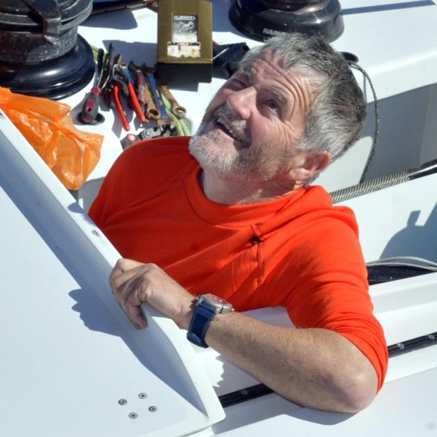 Irish sailor Enda O'Coineen watches as a replacement mast is mounted on his racing yacht,...
