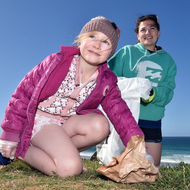 Avana (7, left) and Trinity (16) Martika, of Mornington, pick up rubbish from John Wilson Ocean...