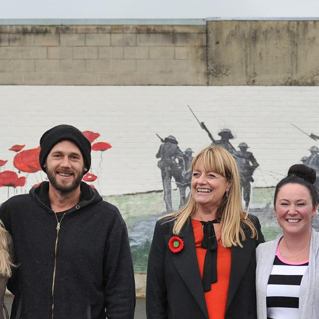 At a new Anzac-themed mural in Mosgiel yesterday are (from left) artists Tessa Petley and Daniel...