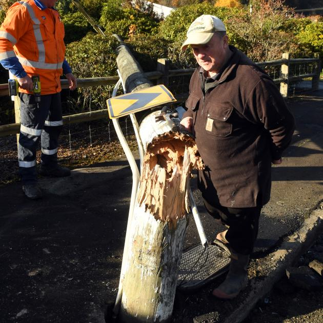 Malvern St resident Bruce Walker checks the damage to the power pole after it was knocked over...