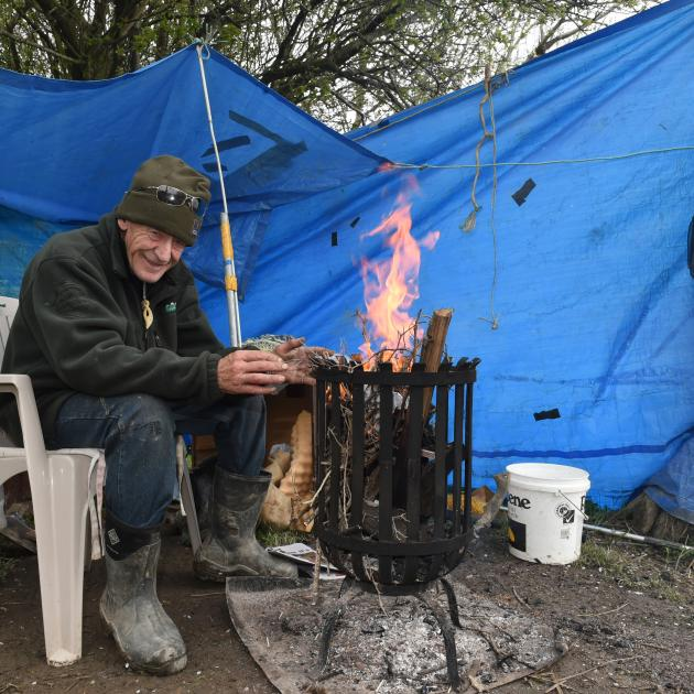 John Carvalho warms his hands at an open fire as wind and rain buffet his whitebait camp near Henley yesterday. Photo: Gregor Richardson