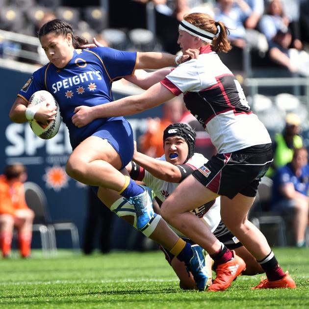 Otago spirit replacement back Kilistina Moata'ane tries to bust through the tackles of North Harbour players Laishon Jones (on ground) and Sophie Fisher at Forysth Barr Stadium on Saturday. Photo: Peter McIntosh