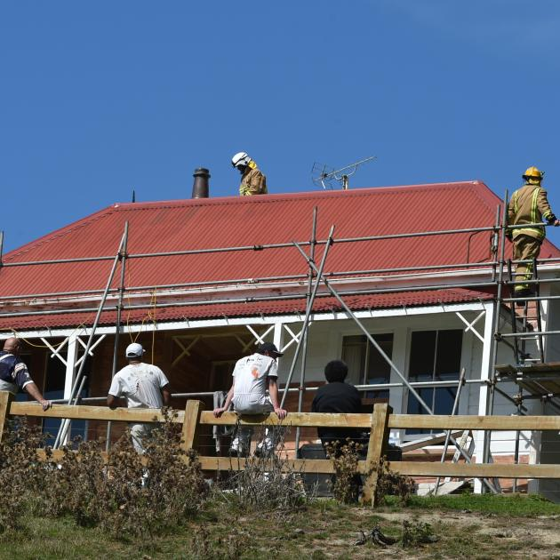 Painters watch as firefighters inspect the house that featured in the Robin White work A Buzzy...