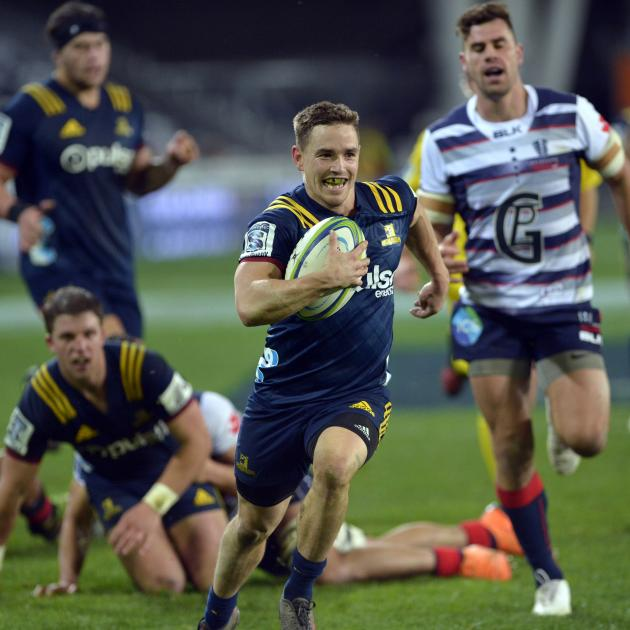 Highlanders halfback Kayne Hammington beams as he speeds to the line to score during Saturday...
