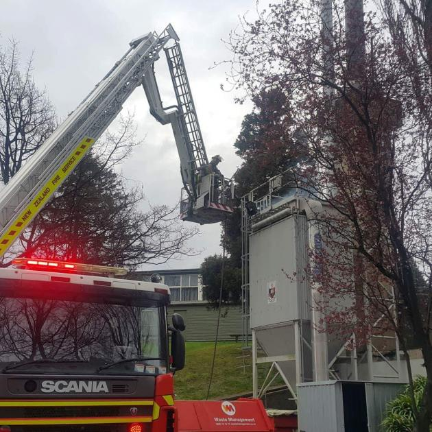 Firefighters tackle a fire in the smoke stack of a boiler at Kaikorai Valley College. Photo:...