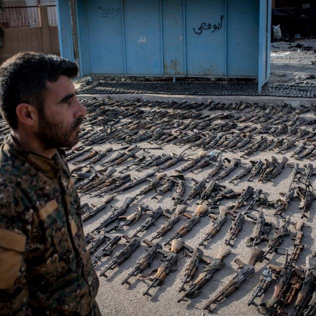 A Syrian Defence Forces soldier looks over seized ISIS weapons in the Syrian town of Beghouz....
