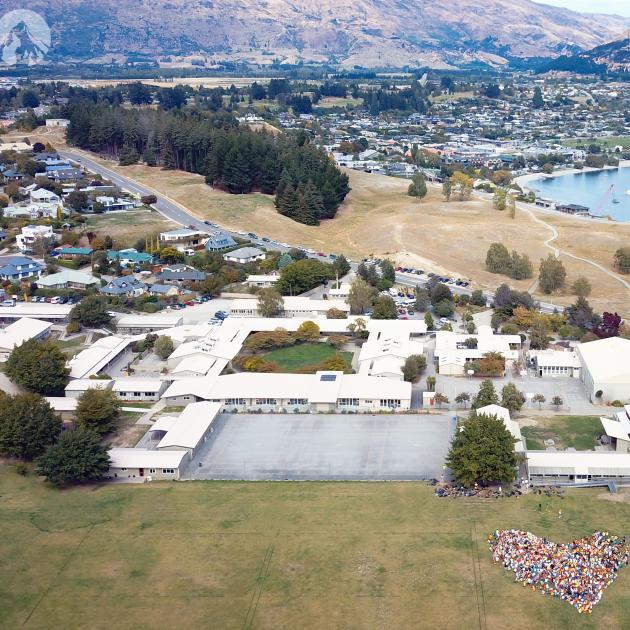 Mount Aspiring College pupils and staff stand together on the school field in the shape of a...