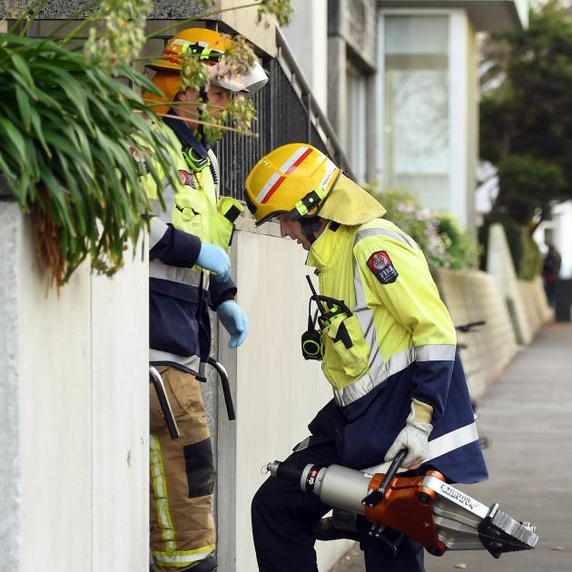 A firefighter carries cutting equipment into Dunedin Hospital after a man was stuck in an X-ray machine in 2017. Photo: Stephen Jaquiery