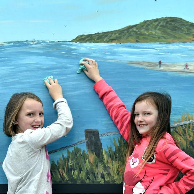 Taieri Beach School pupils and sisters Dannielle (10) and Indica (9) Hawkins clean the seagull...