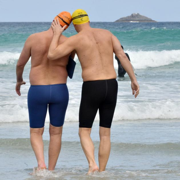 Mr Caughlin (left) is encouraged by friend Gabor Langyel as the pair wade into the St Clair surf....