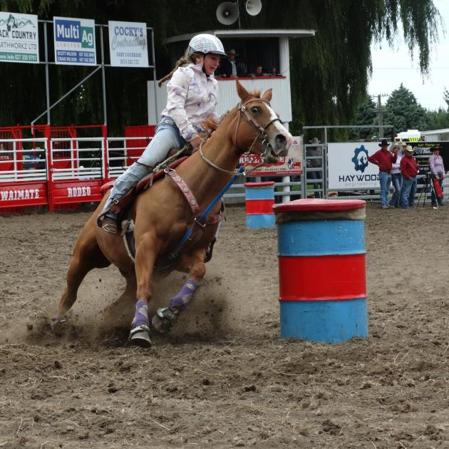 Oamaru's Chloe Ruddle (12) guides her horse around a barrel in the junior barrel race at the...