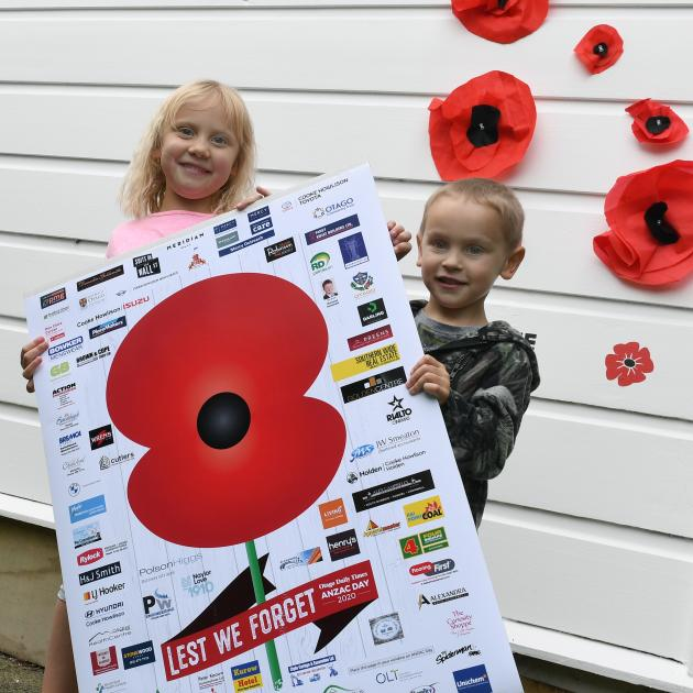 Maleika (5) and Lockie (3) Tuliau hold the Otago Daily Times poppy in front of their own handmade...