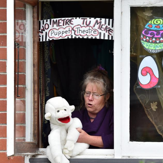 Kaitrin Mcmullan puts on a puppet show for children passing her North East Valley home. PHOTO:...