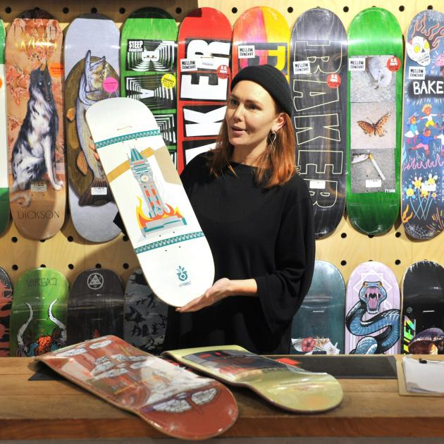 Evie Forno shows off a skateboard painted by Sean Duffel as part of the store's local artist...