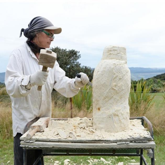 "Moira Crossman working Oamaru Stone to create ""Kahu""."