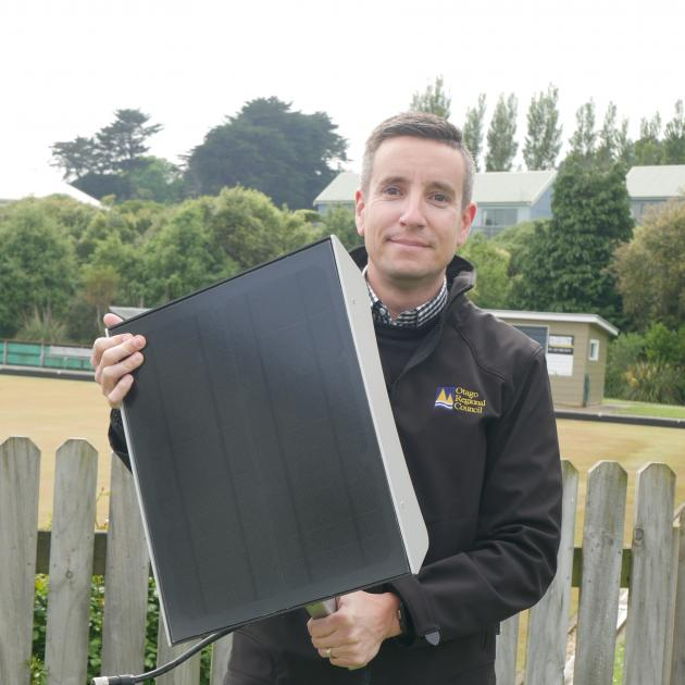 Otago Regional Council public transport team leader Julian Phillips holds a solar panel which...