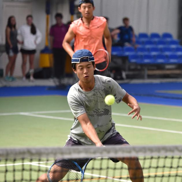 Thomas Hartono volleys the ball, watched by his doubles partner and brother Peter Hartono, at the...