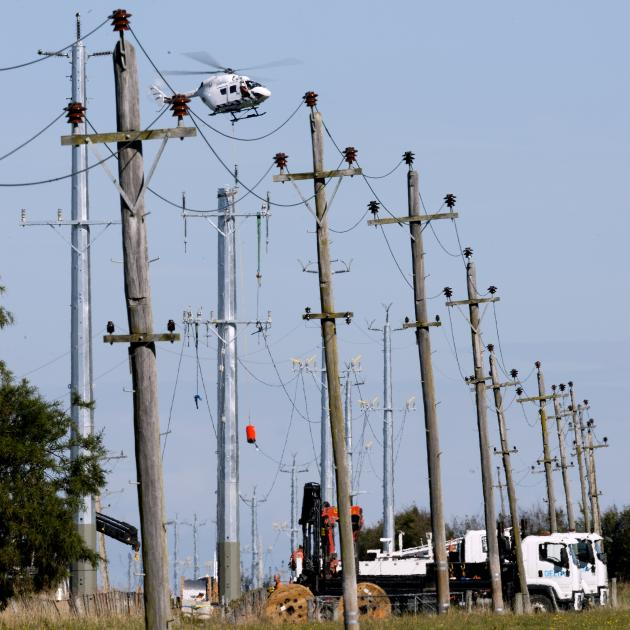 A helicopter positions an electricity line over new poles in Huntly Rd, near Outram, yesterday...