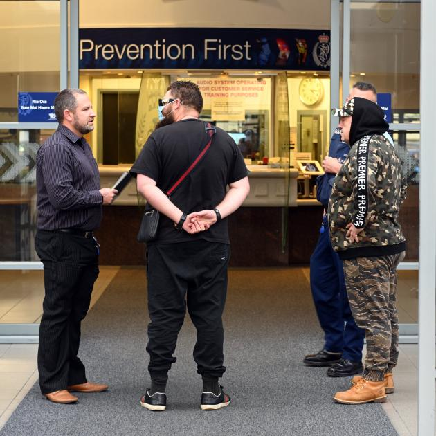 Wanted man James Bryant (centre) is arrested by a Dunedin police officer (left) after handing...