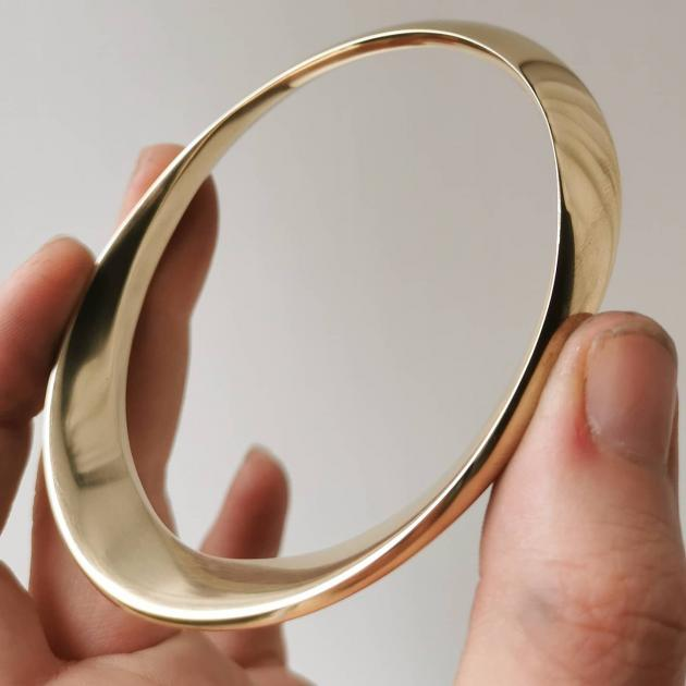 Oval Bangle, crafted from solid 9ct gold is a custom-made piece; refined lines reflect a minimal...