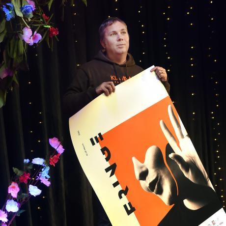 Dunedin Fringe Festival director Gareth McMillan rolls up a poster for the cancelled festival....