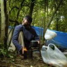 Jolyon White cooks at his bivvy in the Dunedin Town Belt, where he has been living for the past month. Photo by Gerard O'Brien.