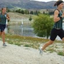 Erin Wilson leads her Columba College colleague Shannon Edgar on the run leg on the shore of Lake Dunstan. Photo by Matt Haggart.
